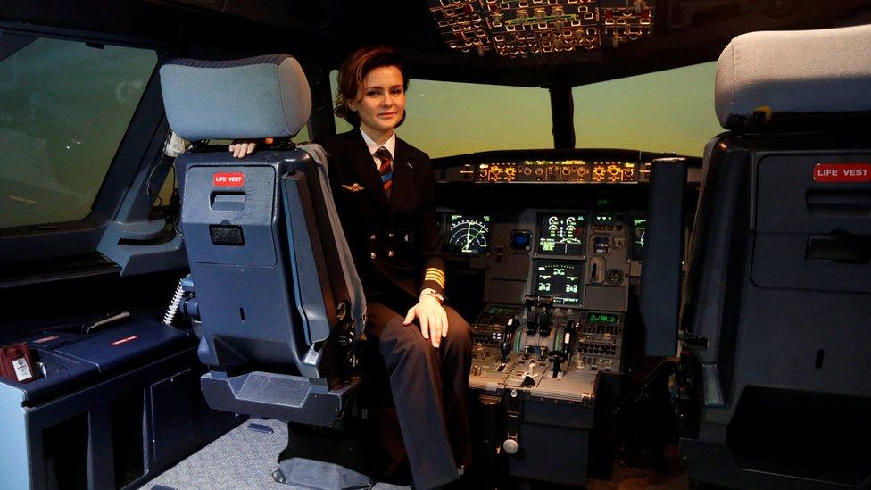 إحدى العاملات في الشركة في جهاز محاكي الطيران