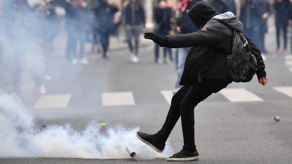 محتج يركل قذيفة غاز مسيل للدموع بعيدا عن موقعه خلال الاحتجاجات
