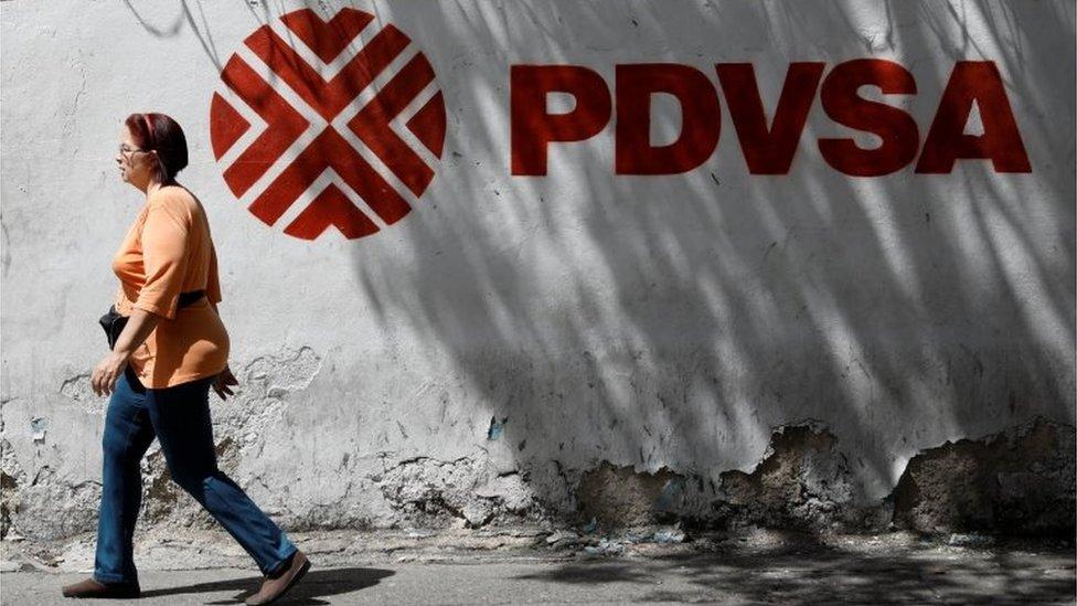 Una mujer camina junto a un cartel de PDVSA en Caracas.