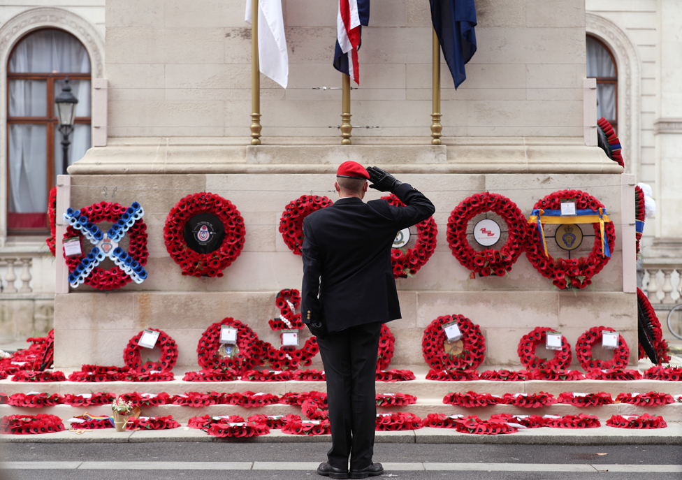A member of the armed services gives a salute at the Cenotaph