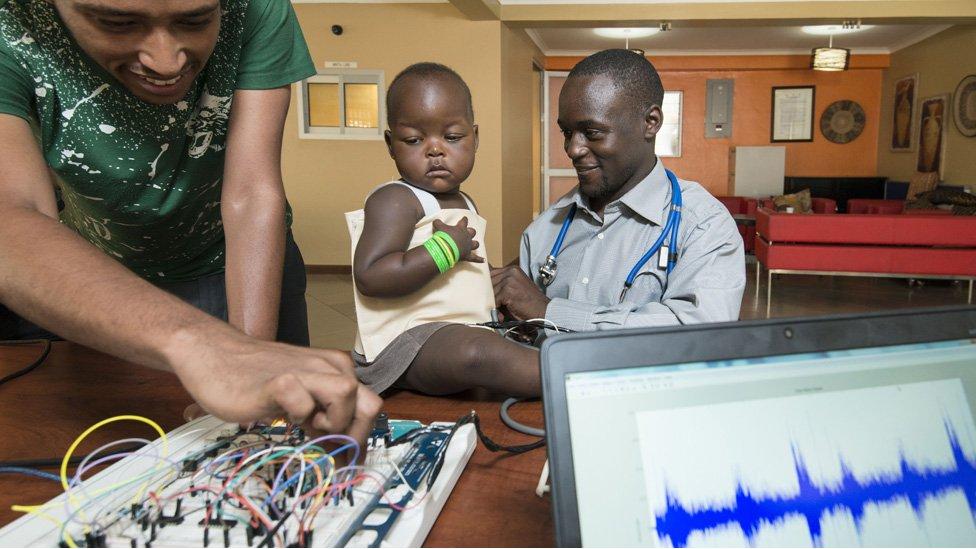 Un niño usando la chaqueta para detectar neumonía y Brian Turyabagye (a la derecha)