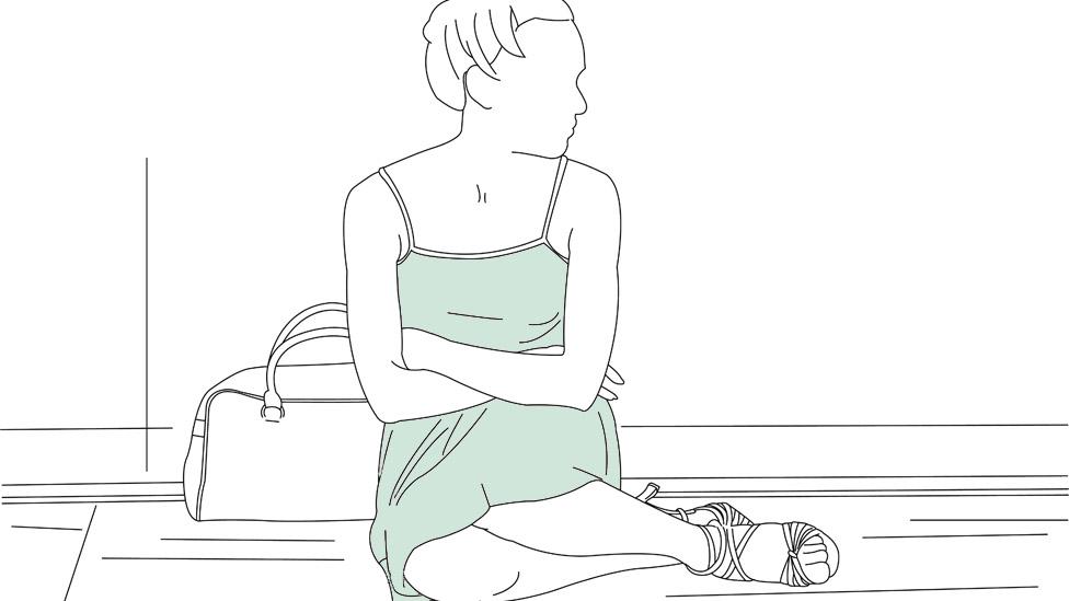 Mujer sentada en el suelo.