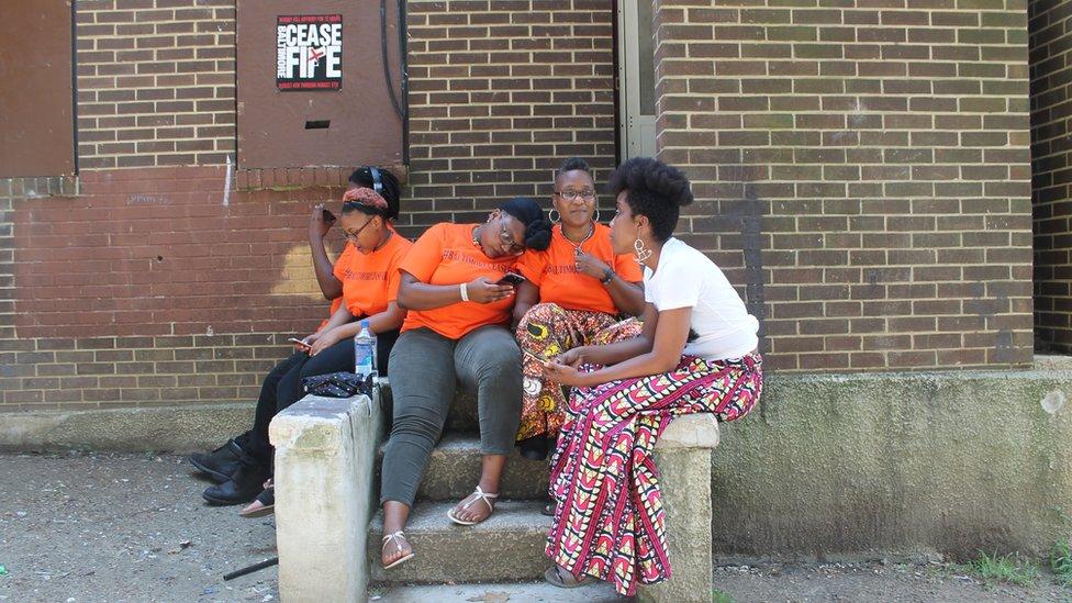 Erricka Bridgeford, tengah kanan, duduk dengan temannya, Ellen Gee, kanan, dan anak-anaknya di luar rumah gudang yang ditinggalkan.
