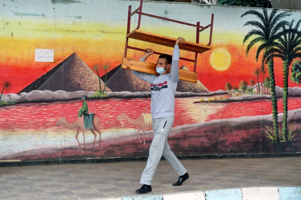 A man carries a bench outside a school, which has a mural painted on a wall.