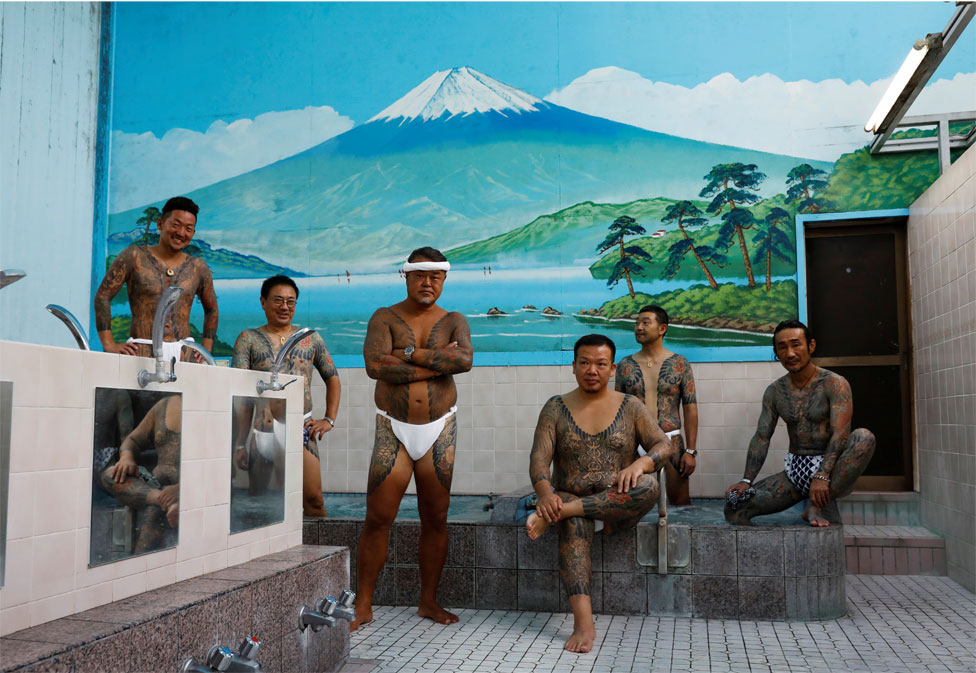 A group of men with tattoos pose in a public bath
