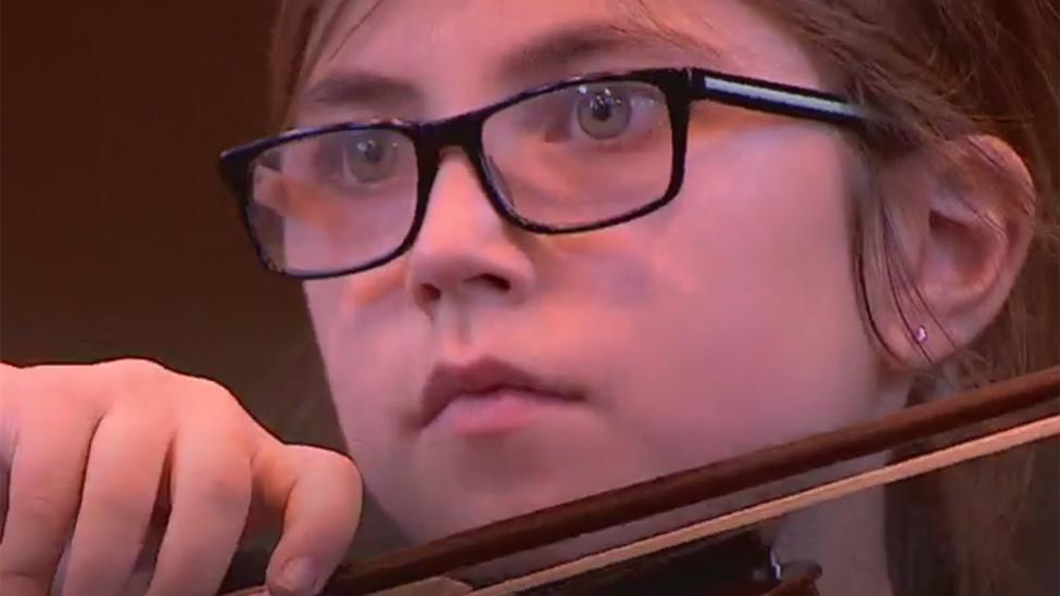Niña tocando el violín.