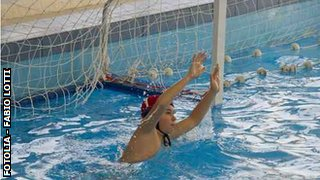 Boy defending goal playing water polo.