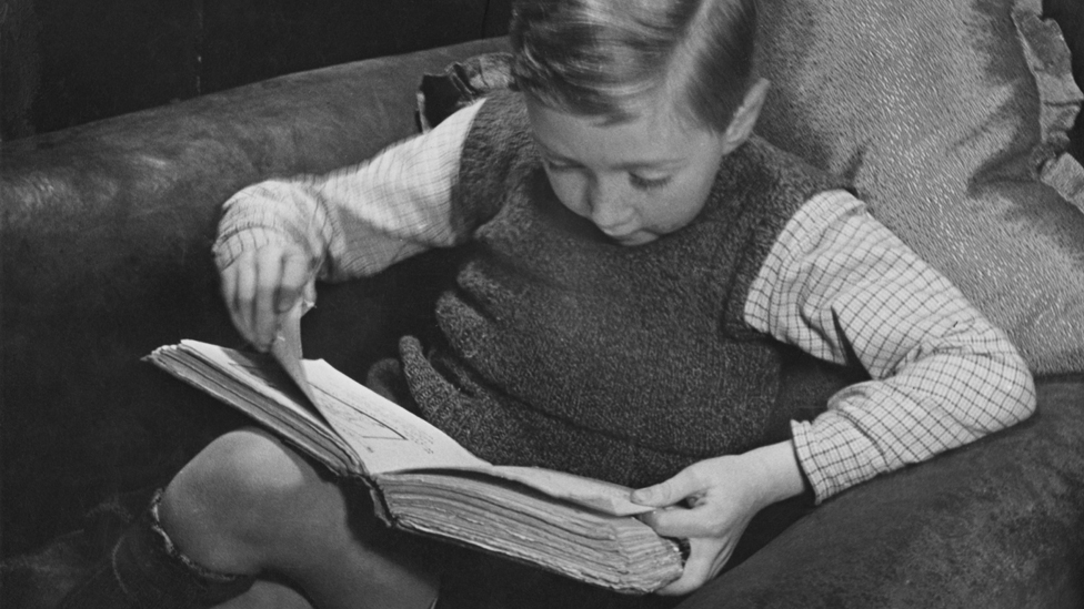 Small boy reading book, 1930s