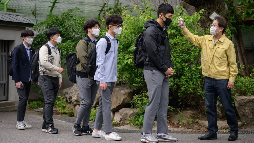 Students returning to school in Seoul in May, wearing face masks and having their temperature checked, after more than two months off due to the pandemic