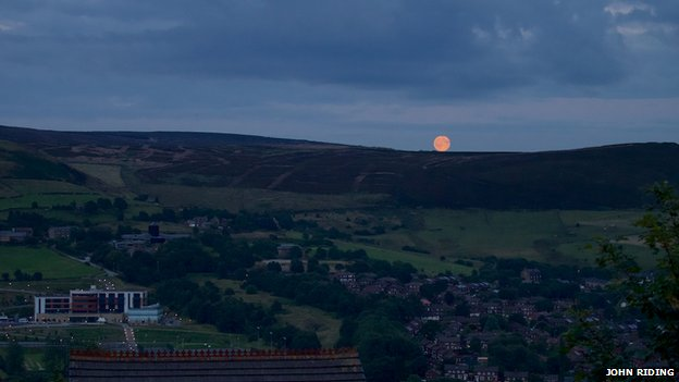 The blue moon disappeared behind hills in Lancashire.