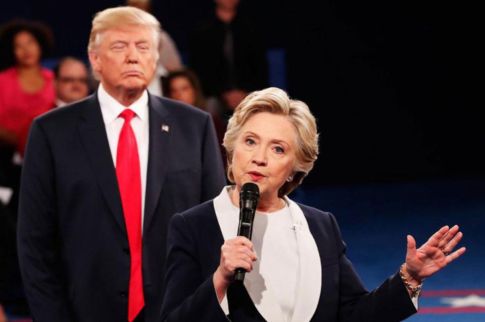 Donald Trump se para detrás de Hillary Clinton durante uno de los debates presidenciales.