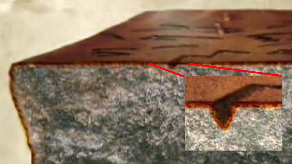 Roca con pátina y detalle de la letra