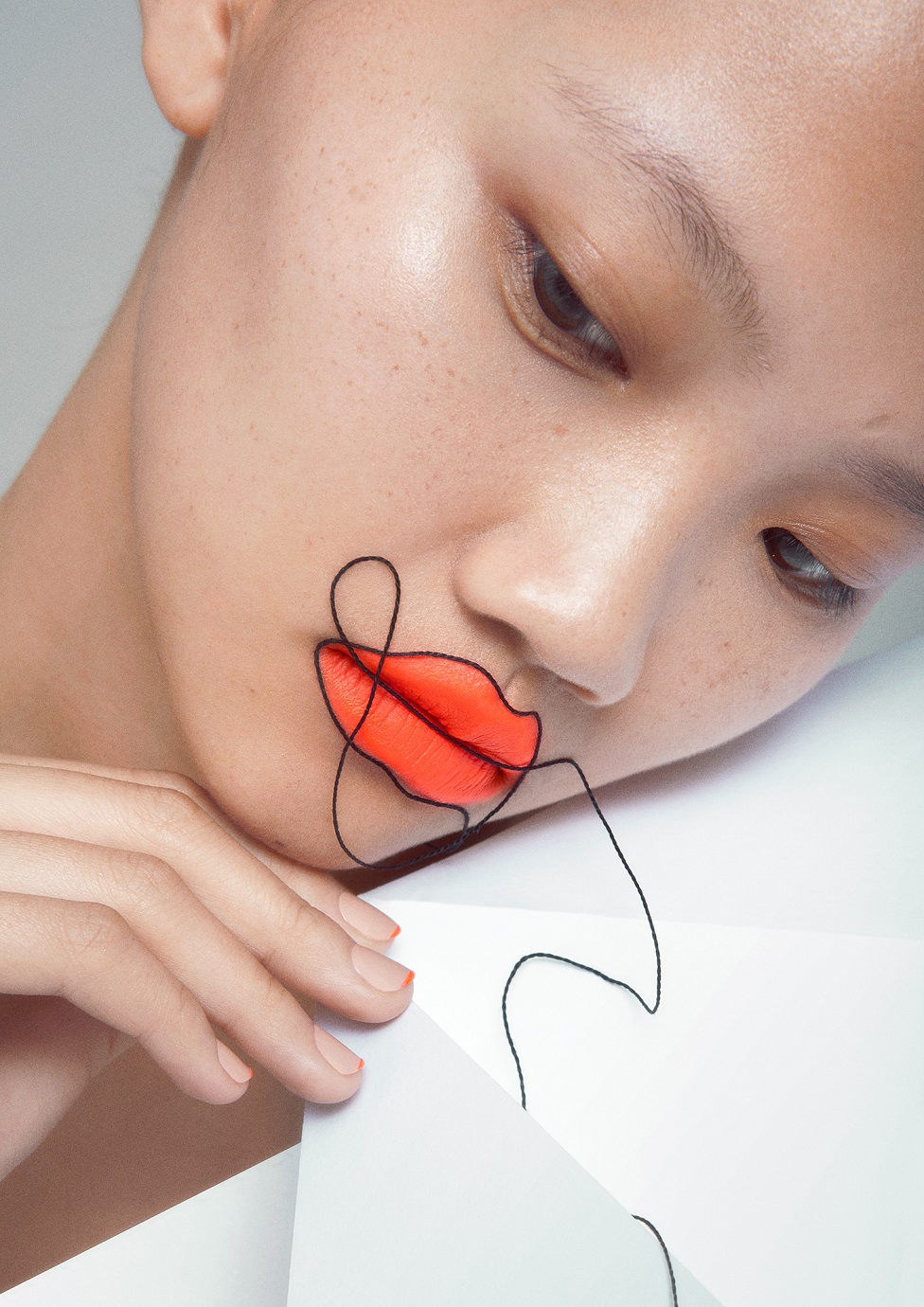 A model poses with bright lipstick and a thread running over her face and around the outline of her lips