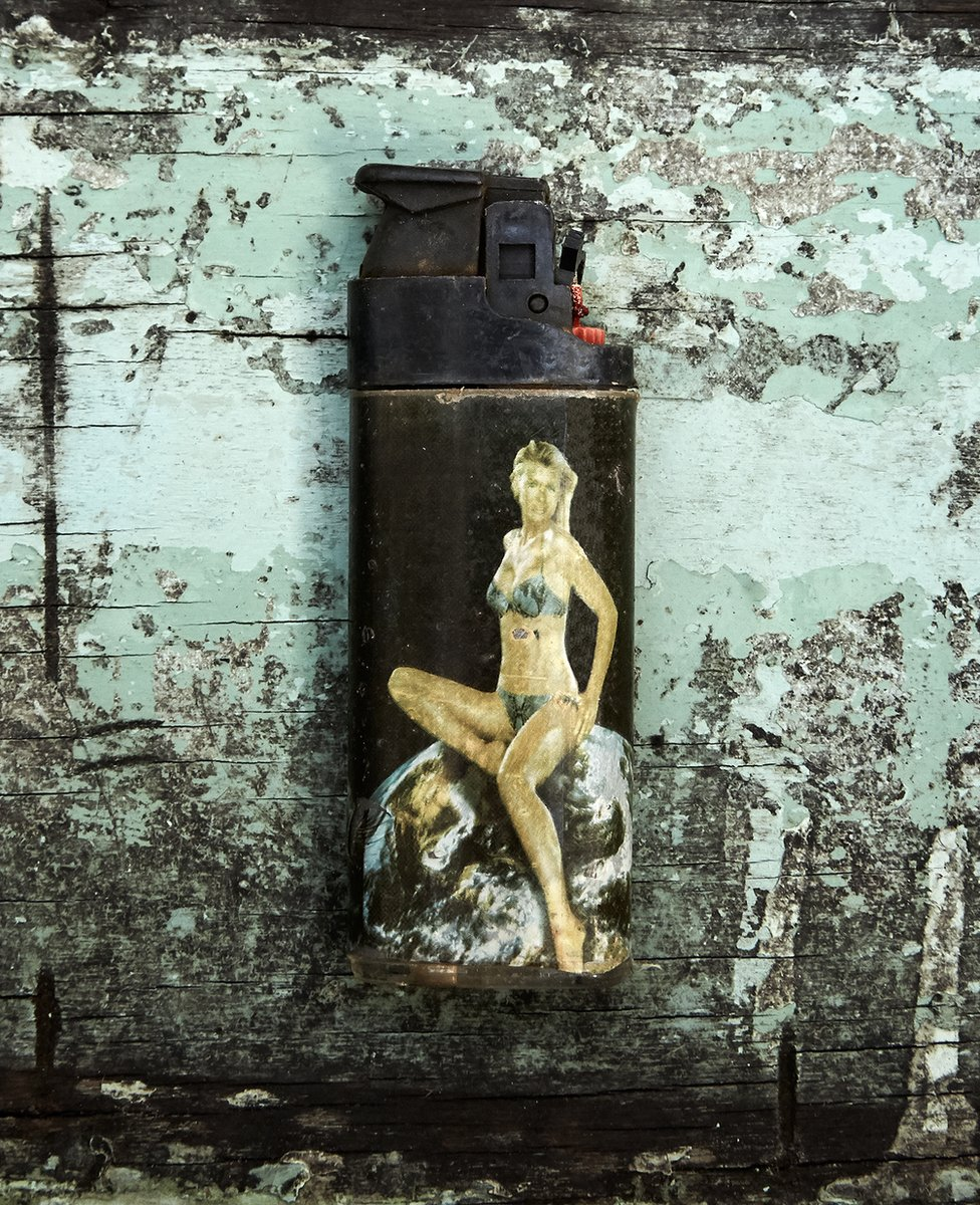 A scuffed and worn plastic lighter retrieved from the sea, featuring a bikini-clad woman sitting on an image of the Earth
