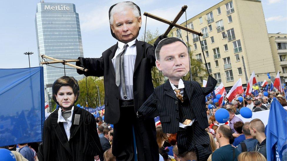 Manifestantes con fotos del líder del PiS, Jaroslaw Kaczynski (centro), de la primera ministra Beata Szydlo (izquierda) y del presidente Andrzej Duda (derecha), durante la Marcha por la Libertad, en Varsovia, en mayo de 2017.