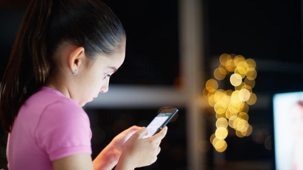 niña usando internet en su teléfono