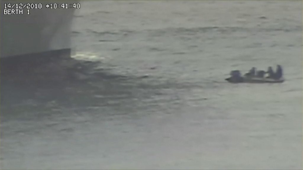 Stricken inflatable boat faces cruise ship head on