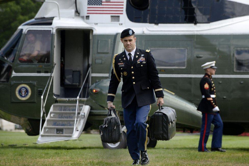 Agente de seguridad portando el maletín nuclear.