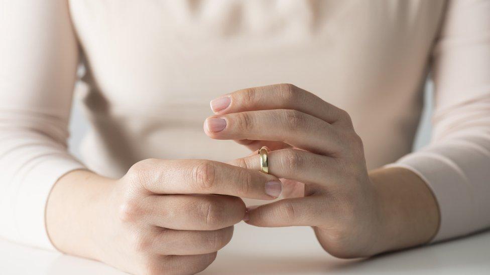 Mujer sacándose alianza matrimonial.