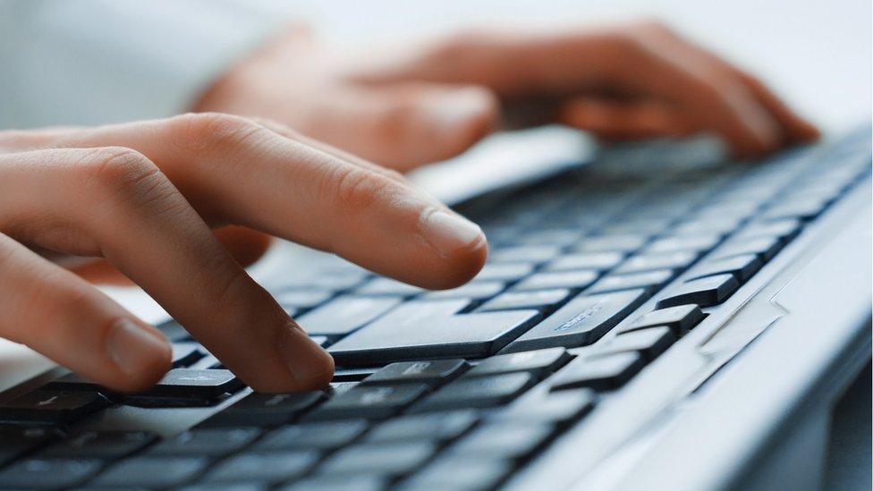 Un hombre escribiendo en una computadora.