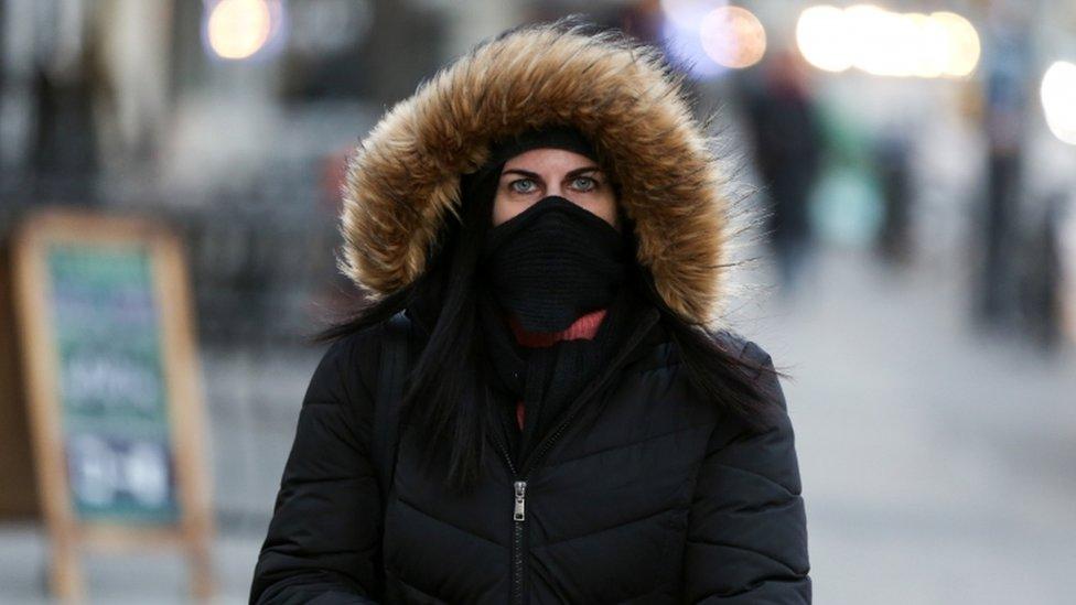 Mujer con una capucha y la cara cubiera por el frío.