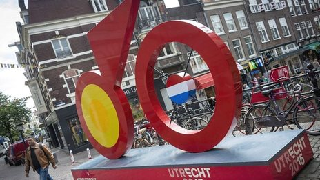 A man walks past a giant imitation bicycle, painted red, as Utrecht prepares to host the Tour de France