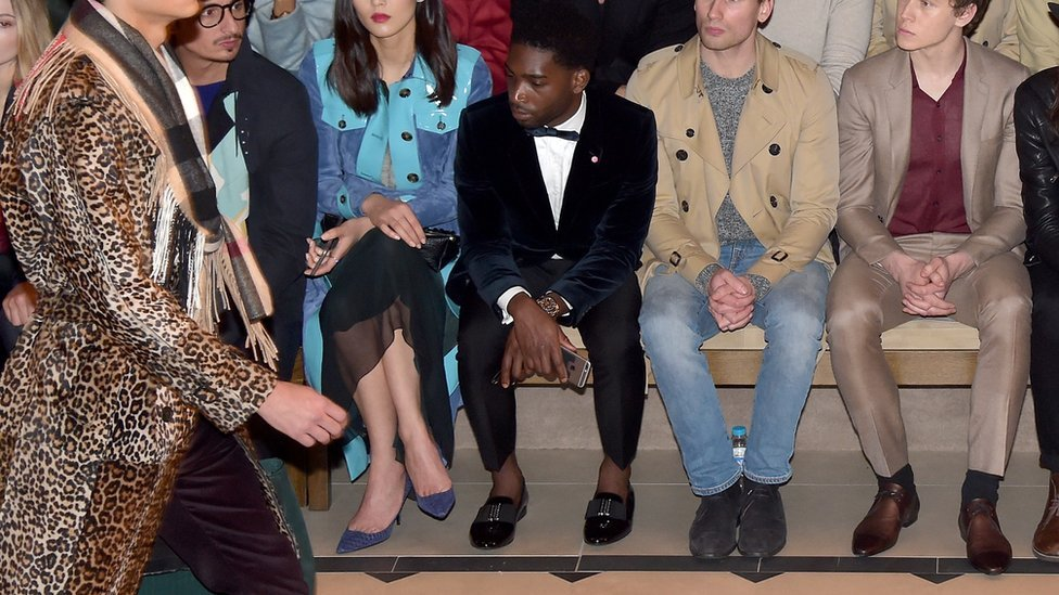 El cantante británico Tinie Tempah, mostrando sus tobillos en primera fila de un desfile de moda.