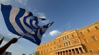 A protester waves a Greek flag during an anti-austerity rally in Athens, Greece, on 29 June 2015.
