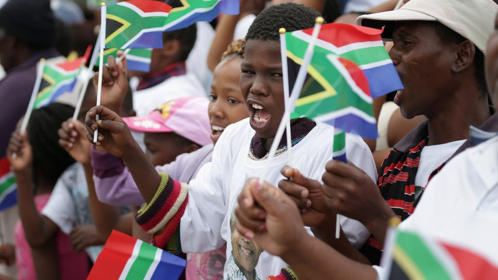Children at Nelson Mandela's funeral sing Nkosi Sikelel' iAfrika and wave flags