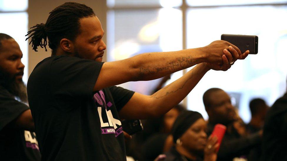 Un asistente a una reunión especial del concejo municipal en Sacramento, California, sostiene un teléfono como si fuera un arma