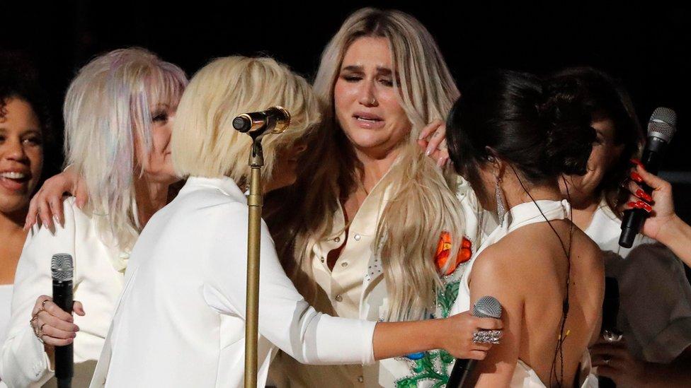Kesha llora mientras sus otras compañeras en la presentación de los Grammy la abrazan.
