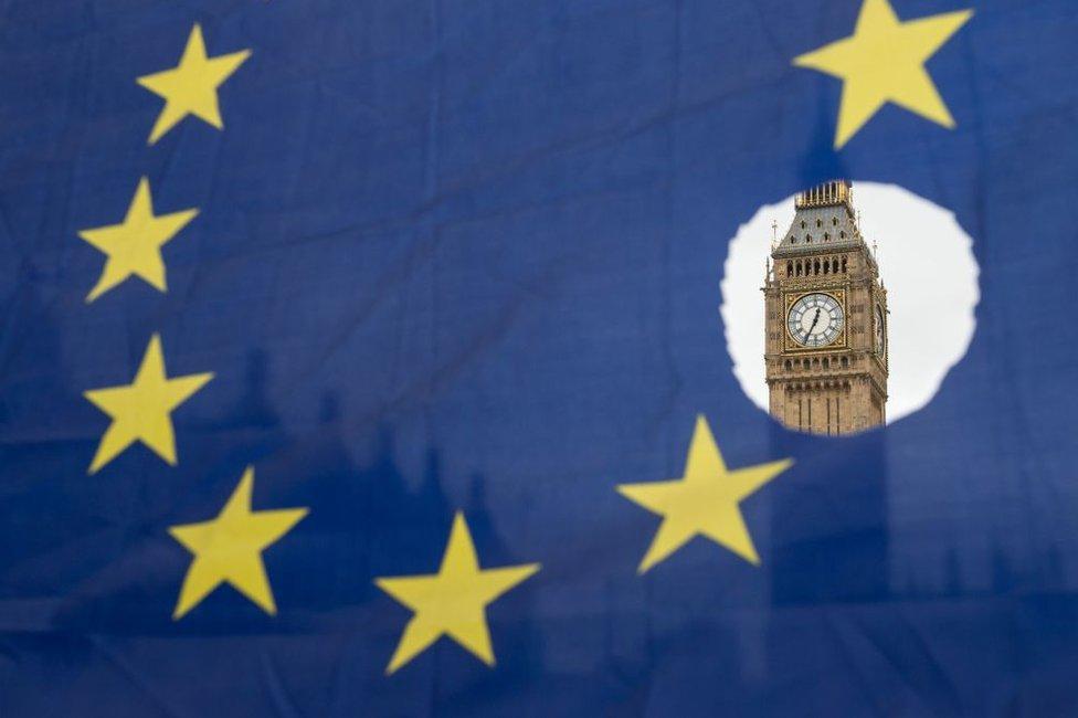 El Big Ben de Londres visto a través de un agujero en la bandera de la Unión Europea.