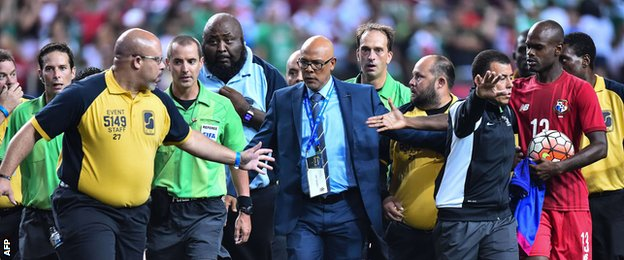 Officials led off the pitch by security