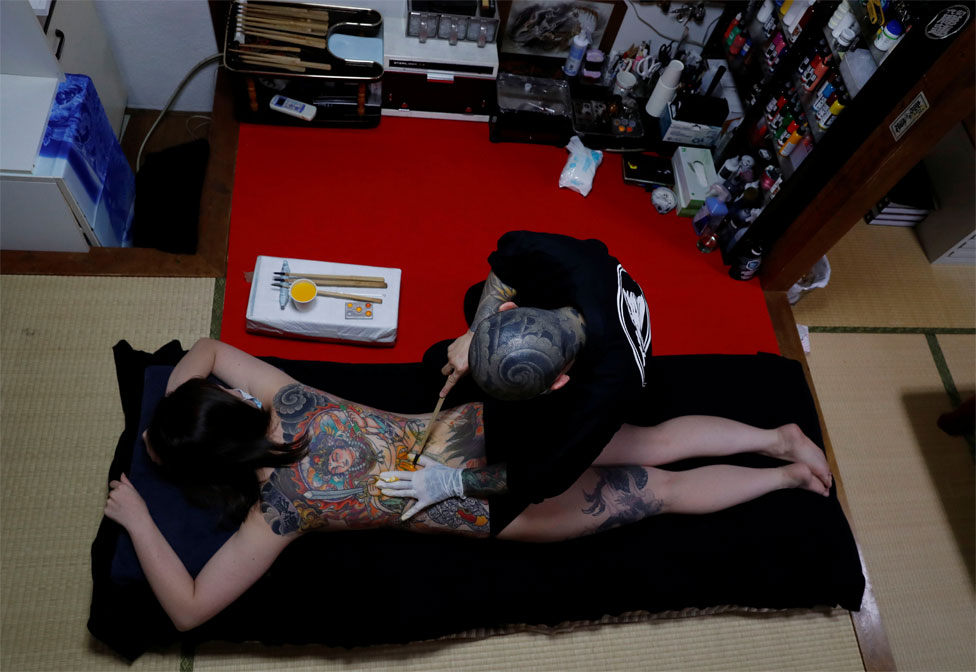 A tattoo artist tattoos a woman's back in their studio