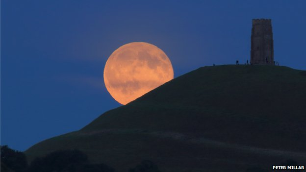 A blue moon slowly rises over the Glastonbury Tor