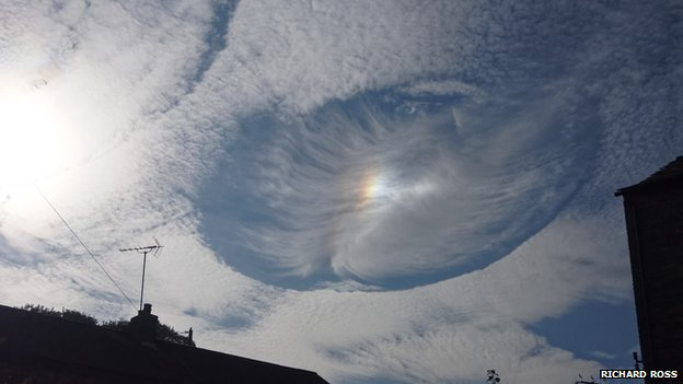 Parhelion in a fallstreak hole over houses on a bright day
