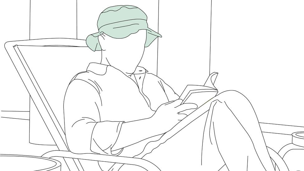 Hombre sentado leyendo.