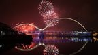Fireworks over an arch bridge. The fireworks are reflected in the still water beneath
