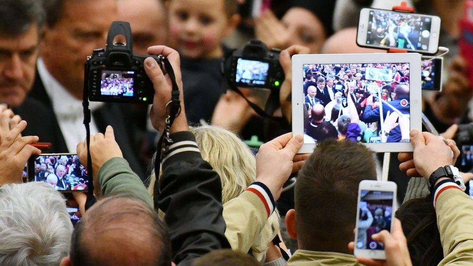 Gente tomando fotos al Papa