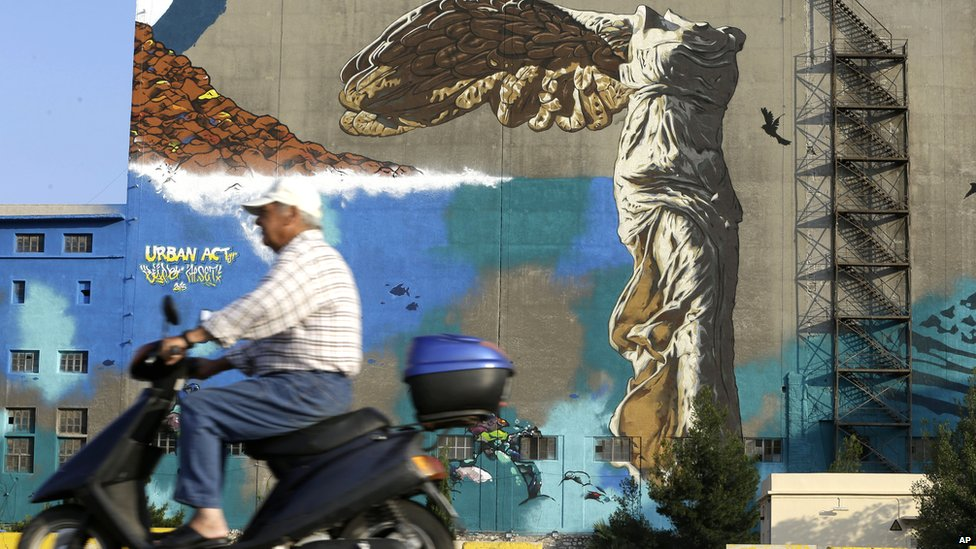 A man drives his scooter past a graffiti depicting The Winged Victory of Samothrace on the wall of an old building at the port of Piraeus, near Athens, on 28 June 2015