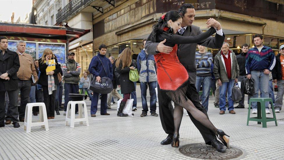 Una pareja de bailarines profesionales bailan en tango en una calle de Buenos Aires.