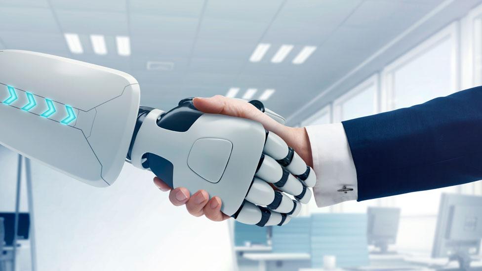 Un robot y un hombre se dan la mano
