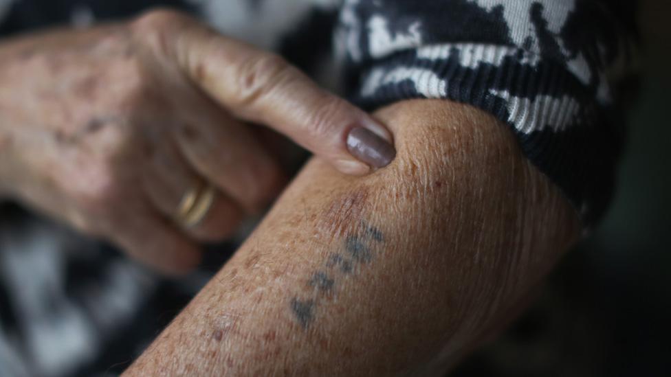 Finger points to Auschwitz tattoo on arm