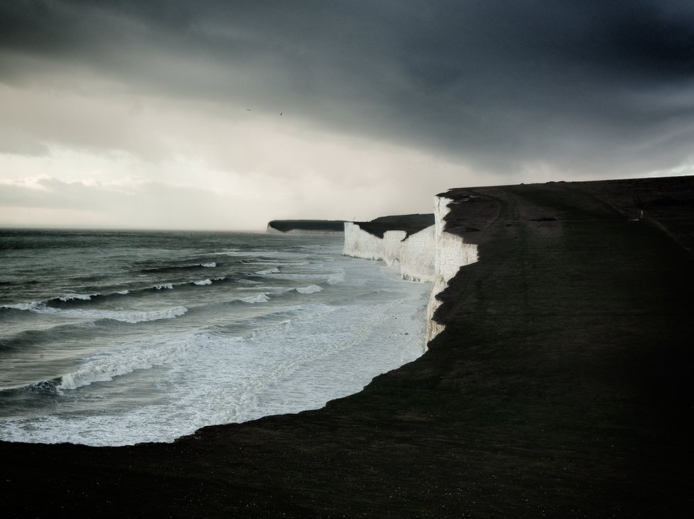 A view of white cliffs with a dark and rough sea beneath