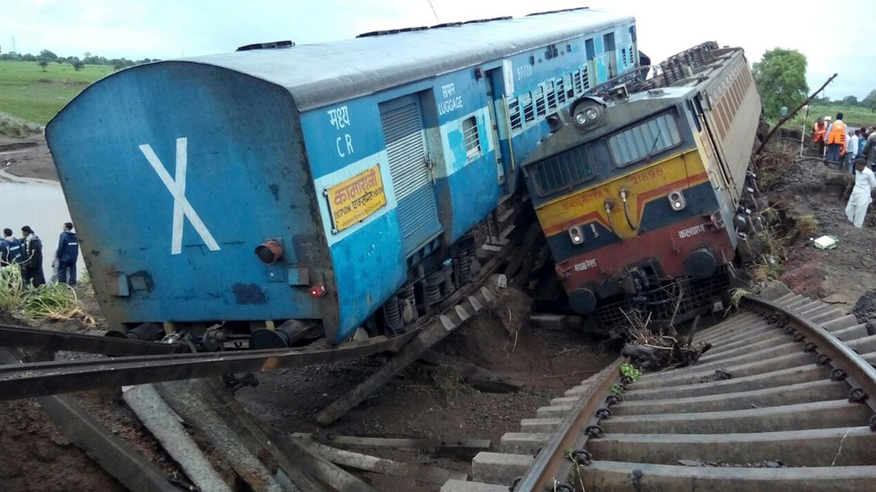 Two passenger trains in the Indian state of Madhya Pradesh derail on a partially flooded bridge, killing at least 24 people, officials say.