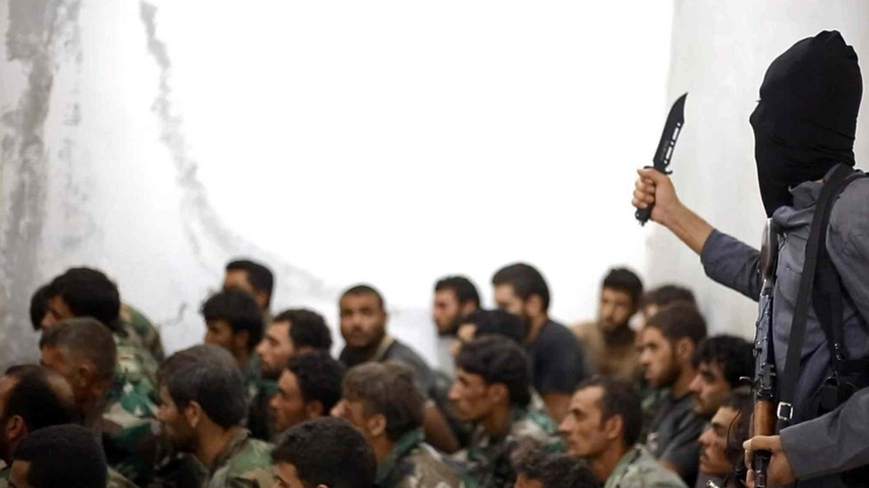 An Islamic State fighter gestures with a knife while addressing captured Syrian soldiers after the fall of Tabqa airbase in Raqqa province (27 August 2014)
