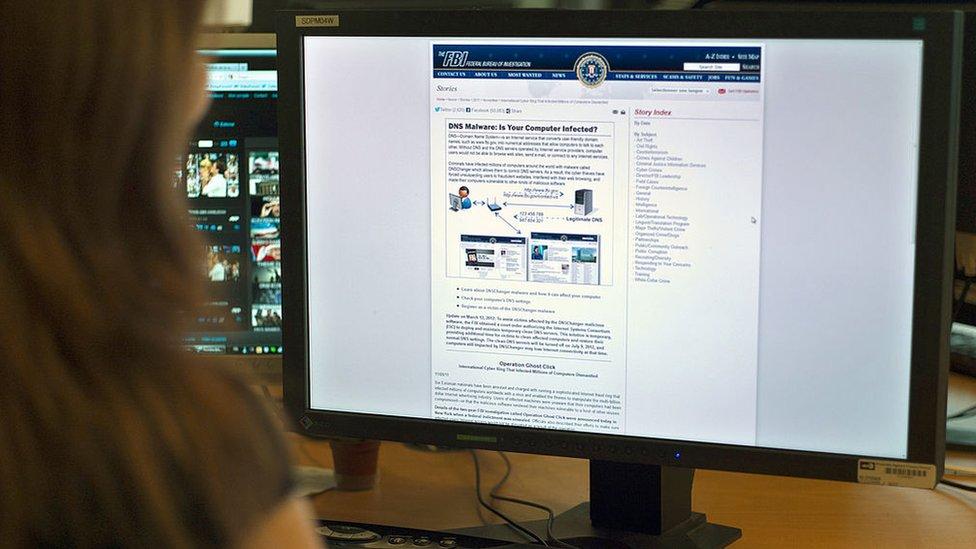 Una mujer frente a una computadora.