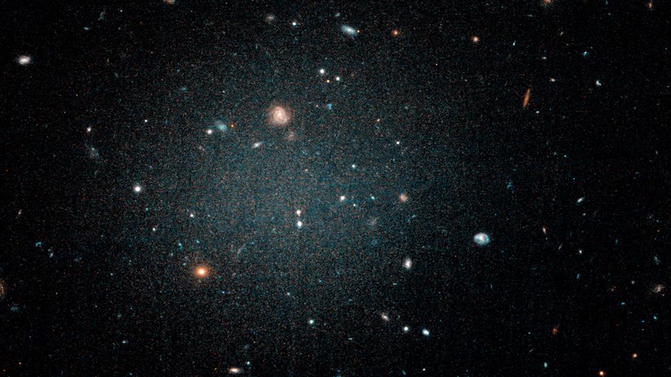 Una burbuja borrosa con otras galaxias que pueden verse a través de ella.