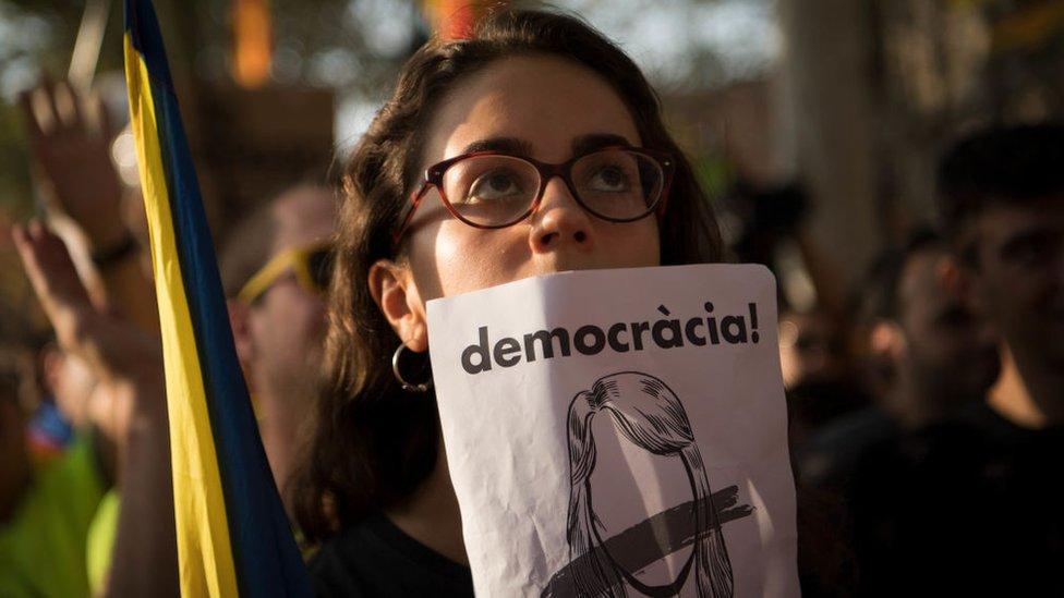 Mujer con cartel pidiendo democracia en Cataluña.