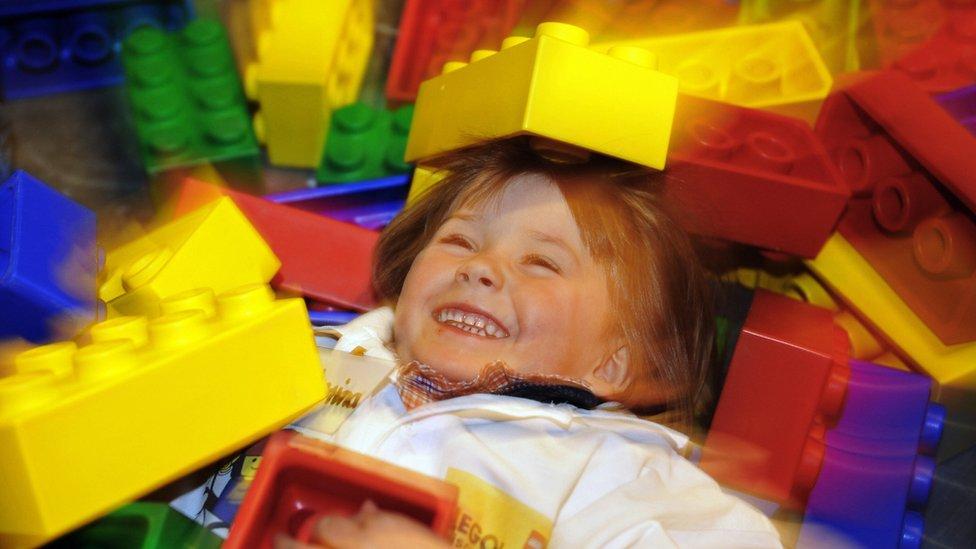 Niña jugando entre bloques grandes de Lego